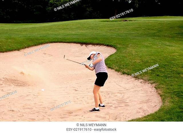 Frau spielt Golf auf einem Golfplatz