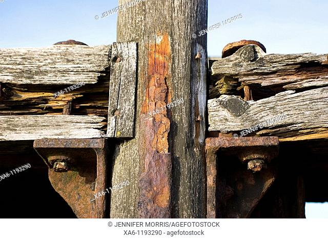 A rusted metal and wood pier on the beach