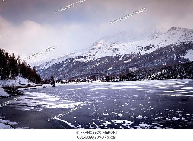 Frozen lake and village beneath snow covered mountain, Engadin, Switzerland
