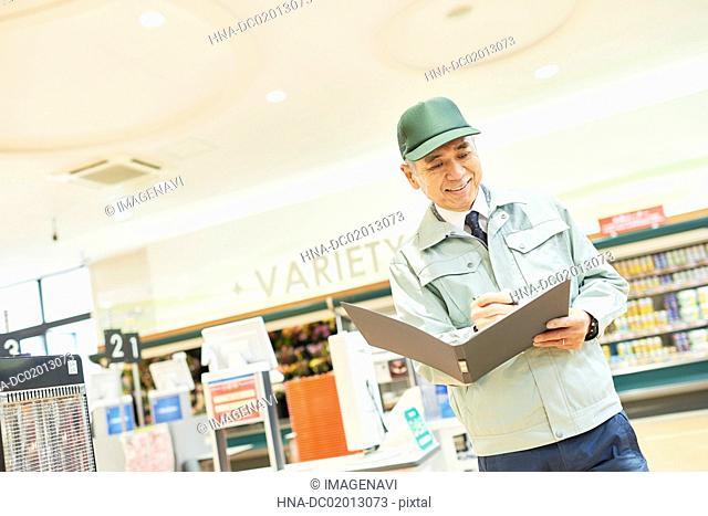 Senior man manager in supermarket (stock control)