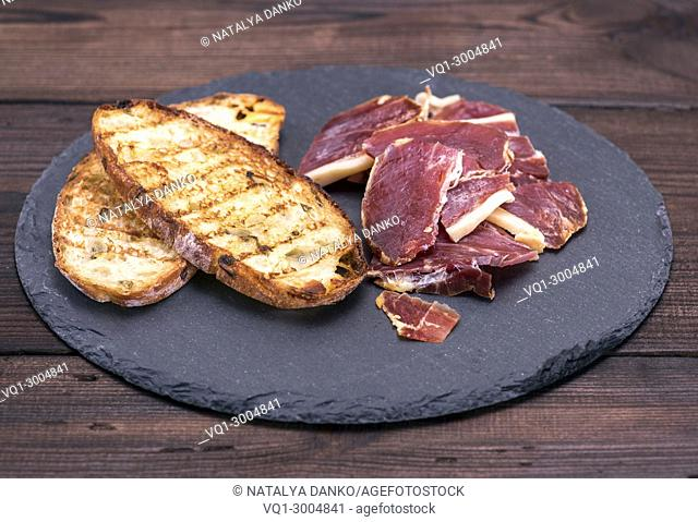 pieces of jamon and bread toast on a black background, top view