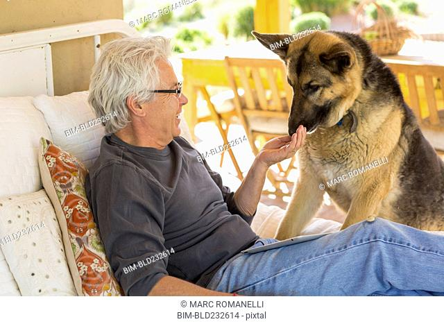 Caucasian man petting dog on patio