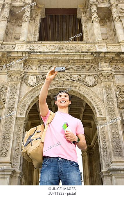 Man taking photograph of himself by archway, smiling, low angle view