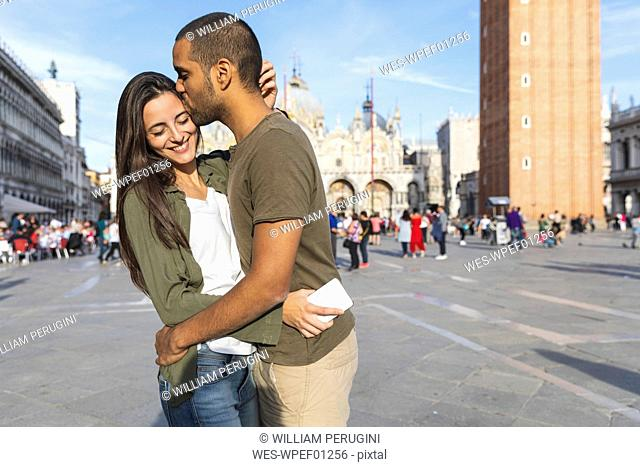 Italy, Venice, happy tourist couple kissing on St Mark's Square