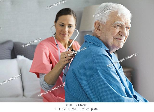 Senior man being examined by home care nurse