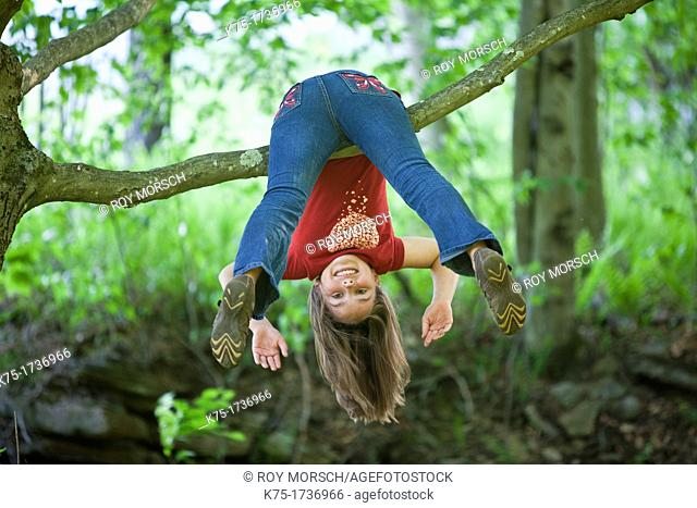 Young girl hanging upside down on branch of tree