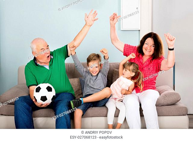 Family Of Soccer Fans Watching Football Match On Television With Children