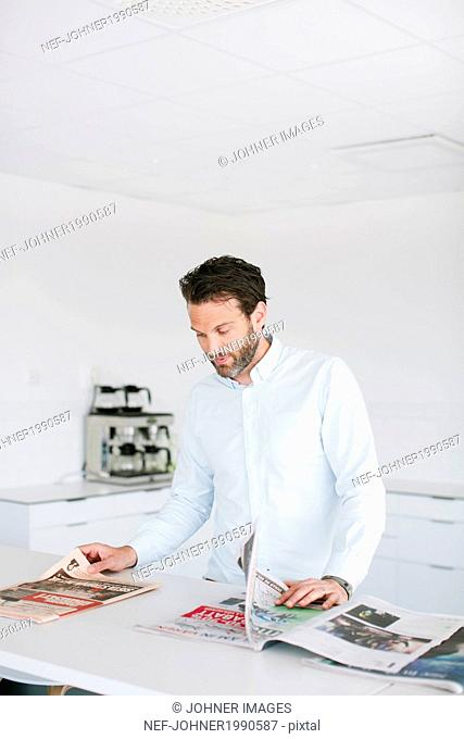 Mid adult man in office reading newspapers