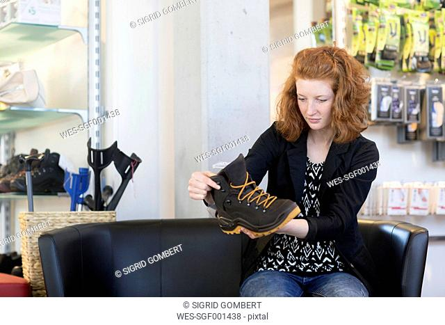 Young woman in shoe shop looking at hiking shoe