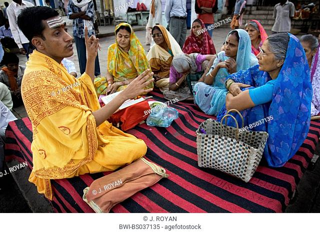 priest with a group of women, India, Varanasi