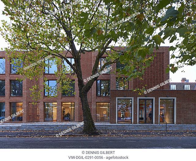 Dusk view towards main entrance with illuminated interiors. Newnham College, Cambridge, Cambridge, United Kingdom. Architect: Walters and Cohen Ltd, 2018