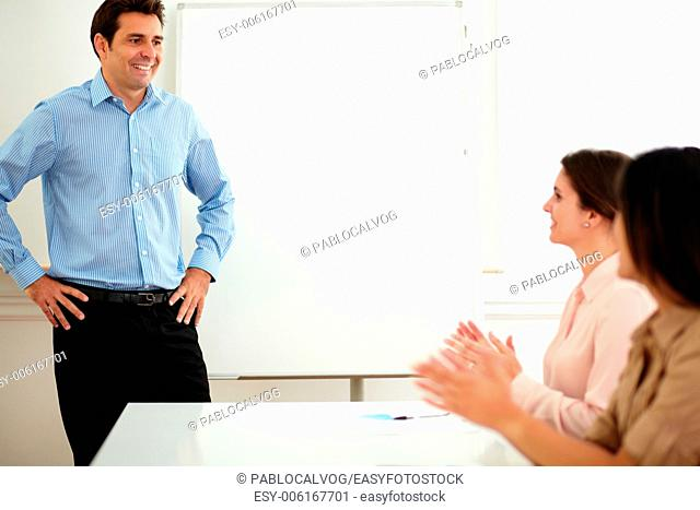 Portrait of businesswomen smiling and giving applause to colleagues on blue shirt during a meeting on office