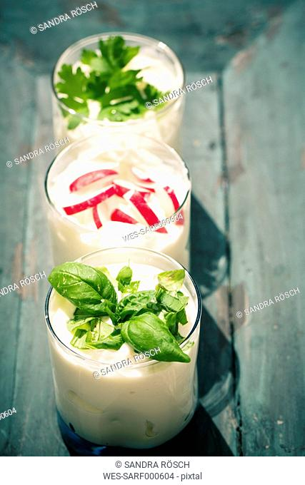 Three garnished glasses of curd with herbs on wooden tray, elevated view