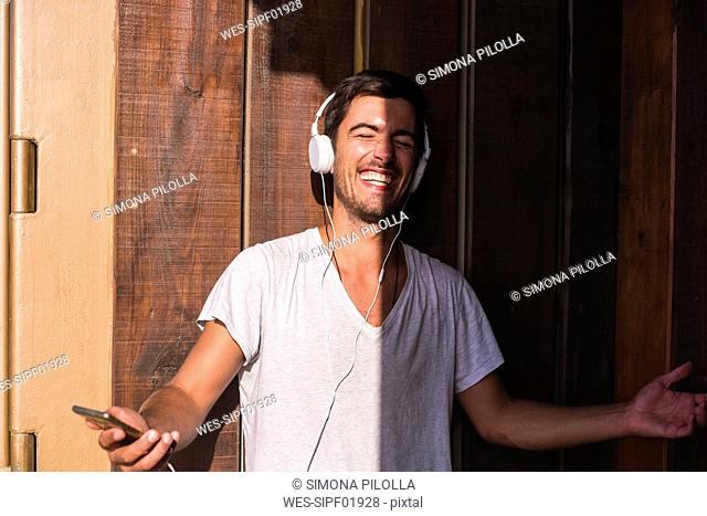 Happy young man with cell phone and headphones at wooden wall