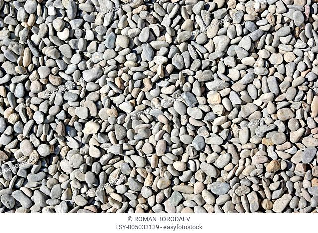 Gray small pebble as background or backdrop. Coastline of Spain