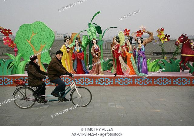 A Chinese couple riding a tandem bicycle past a traditional display, near the Old City wall, Xian, Xi'an, Capital of Shaanxi Province, China