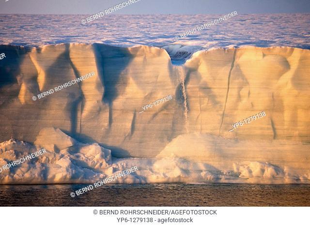 glacier Brasvellbreen in sunset light with waterfall of melt water, Nordaustlandet, Svalbard