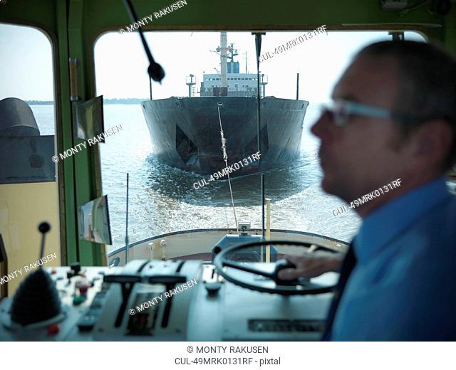 Tugboat pulling ship in ocean