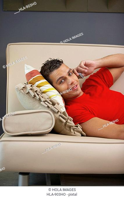 Portrait of a young man talking on a mobile phone and lying on a couch
