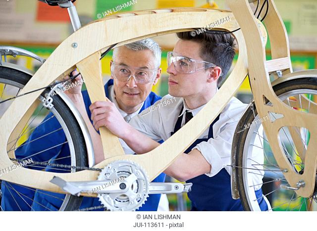 Teacher and high school student assembling bicycle in shop class