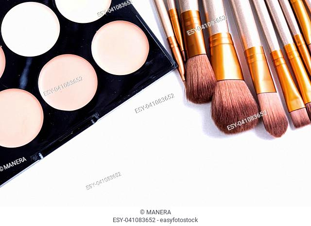 Makeup brushes set and foundation cream palette, beauty professional tools isolated on white background