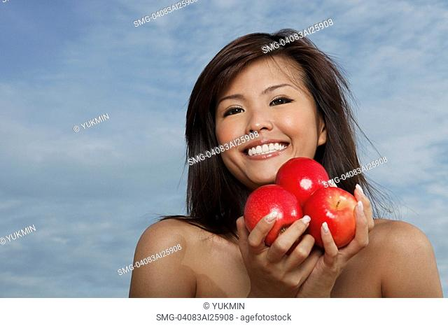 Young woman holding apples and smiling