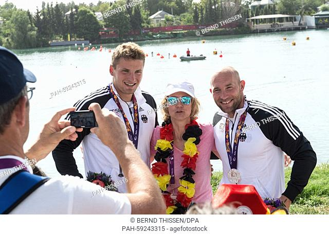 Germany's Ronald Rauhe (R) and Tom Liebscher pose with Heidrun Tempel (C), the German ambassador in Azerbaijan, and their silver medals for the Men's Kayak...