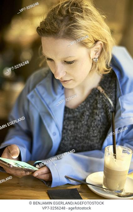 Young woman using phone in cafe, Munich, Germany
