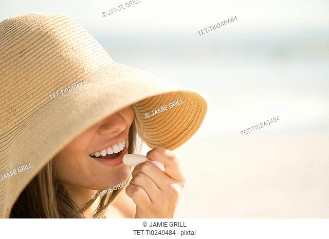 Woman wearing sun hat applying lipstick