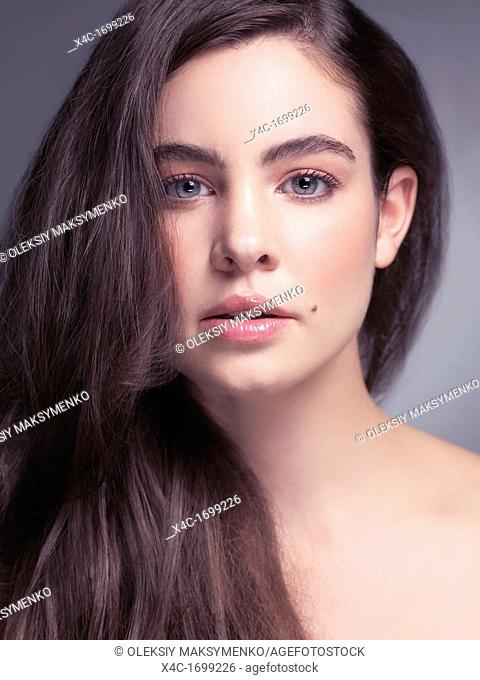 Beauty portrait of a young woman with beautiful gray eyes and long light brown hair