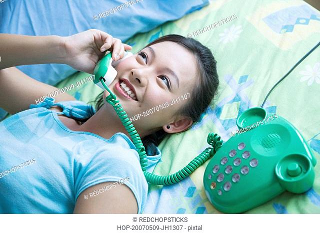 High angle view of a young woman lying on the bed and talking on the telephone