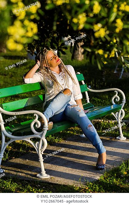 Relaxing on park bench young woman