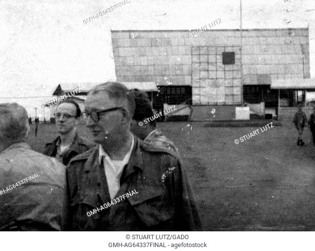 Blurred photograph of American servicemen at an airfield in Vietnam during the Vietnam War, one service men wearing glasses and standing in the front of the...