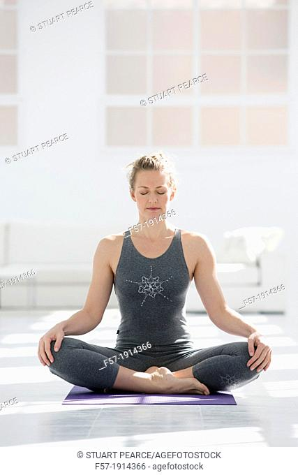 Healthy young woman doing the auspicious pose yoga position