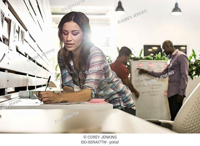 Young businesswoman preparing paperwork in office