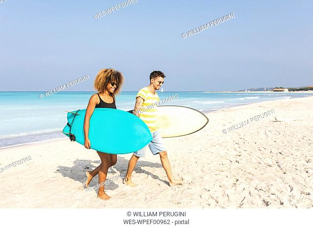 Couple walking on the beach, carrying surfboards