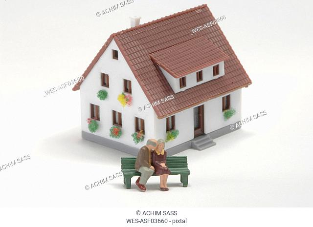Plastic figurines sitting on bench of toy house