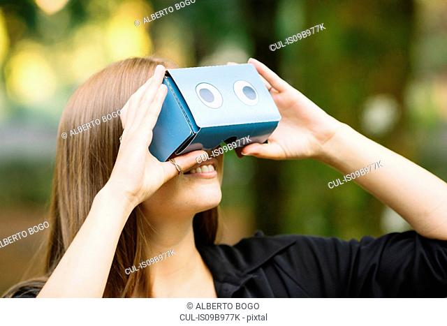 Young woman looking up through cardboard binoculars in park