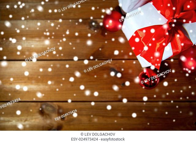 christmas, holidays, presents, new year and celebration concept - close up of gift boxes and red balls on wooden floor from top