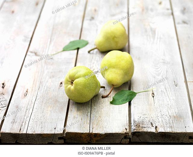 Three pears and leaves on whitewashed wooden table