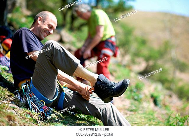 Man sitting on hillside putting on hiking boot smiling