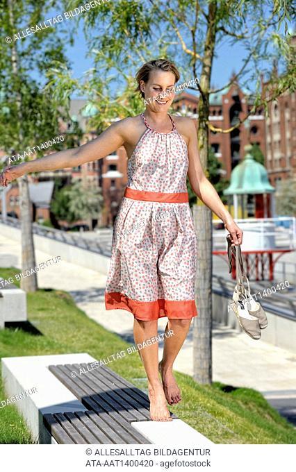 Woman walking barefoot on a wall