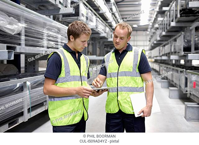 Workers checking orders in engineering warehouse