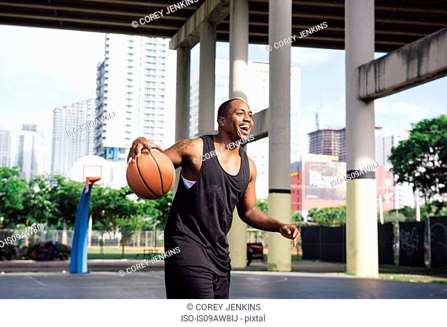 Men on basketball court holding basketball looking away smiling