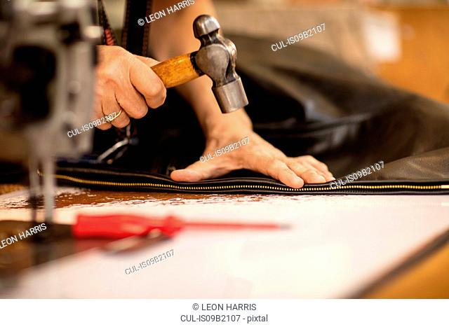 Man hammering zip on jacket in leather jacket manufacturers, close-up