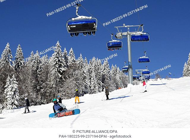 25 February 2018, Germany, Feldberg: Excursionists sit in chairlifts which carries them across a snow-covered landscape in bright sunshine on the Feldberg in...
