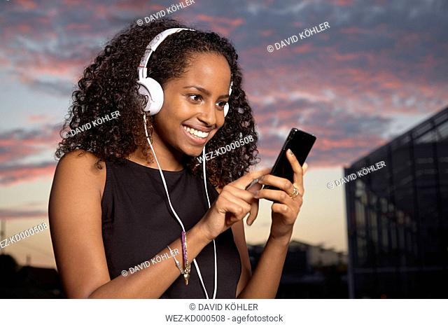 Portrait of excited young woman hearing music with headphones at evening twilight