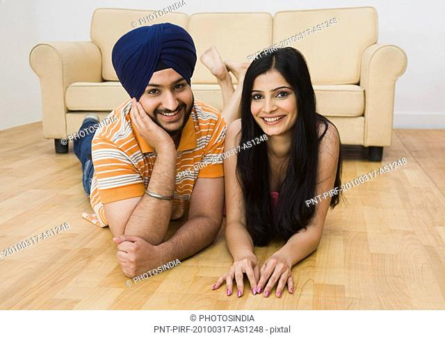 Portrait of a Sikh couple lying on the floor