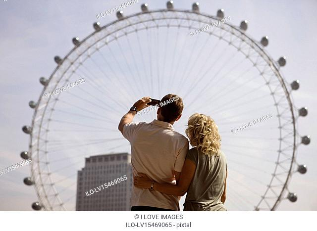 A middle-aged couple photographing the London Eye, rear view