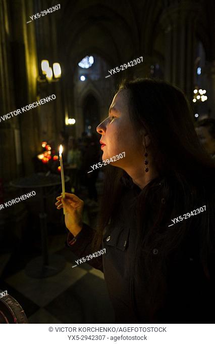 Woman blowing a candle in Notre Dame de Paris